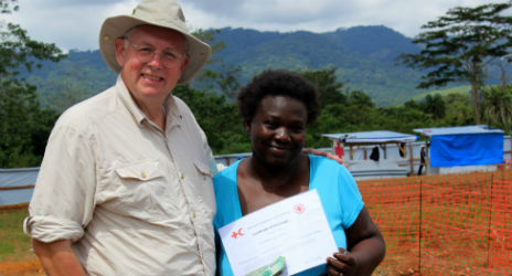 Patricia James (R) has survived Ebola and stands with the director of the Red Cross treatment centre in Sierra Leone with her certificate to prove she is now free of the virus. Photo: Lisa Pattison, IFRC