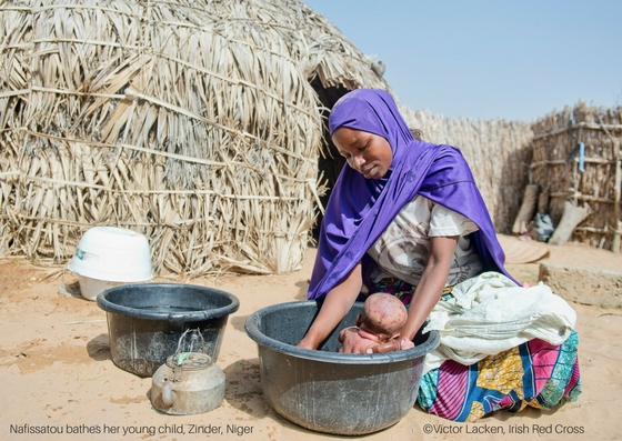 Nafissatou bathes her young child, Zinder, Niger