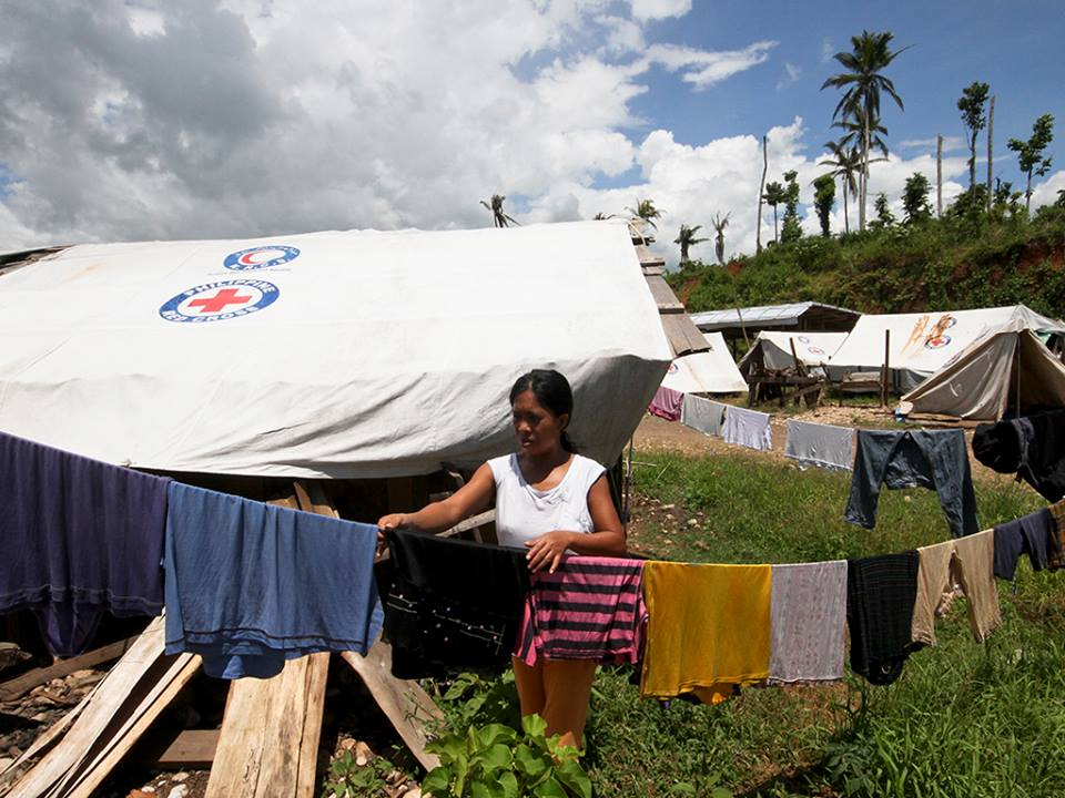 A woman hangs clothes to dry outside her dwelling in the tent city in Cateel. Alanah Torralba/IFRC