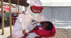 Patrice Gordon, a Canadian nurse, feeds two year old Magdalene, an Ebola patient at the Red Cross treatment centre in Sierra Leone
