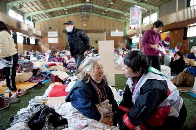 A Japanese Red Cross Worker provides psychological support service to an elderly woman.