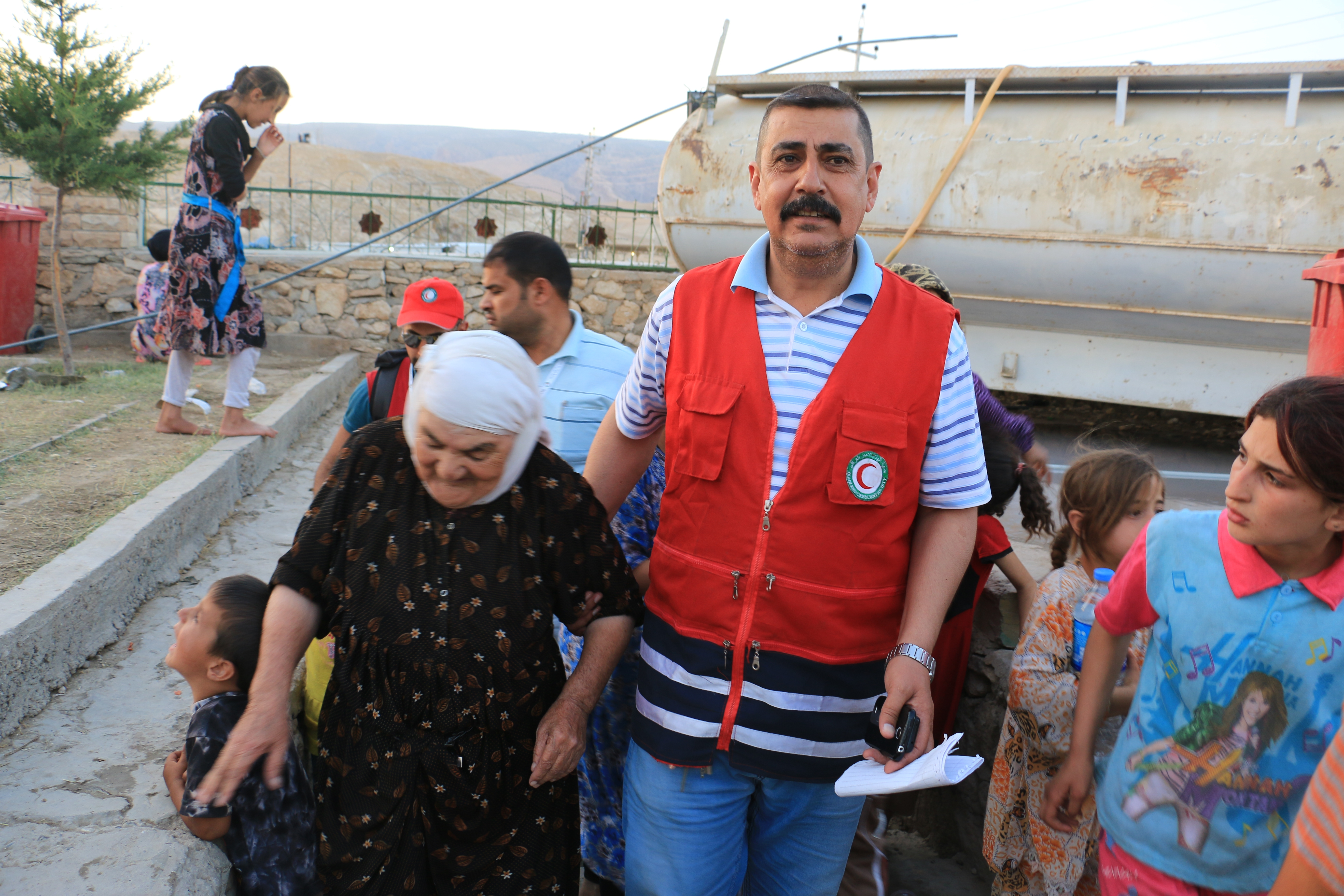 Muhammad Jasem Shariif, the director of Sinjar office of Iraq Red Crescent, helps a woman who has come from Tal Afar. © Ibrahim Malla / IFRC
