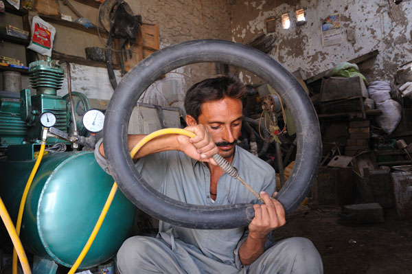 With the help of cash grant from the Pakistan Red Crescent Society and the IFRC, Aziz Ullah was able to open a shop where he repairs punctured tyres for people in his village, located in Sindh Province. The grant was part of a livelihoods project for families affected by Pakistan's 2010 monsoon floods. Photo: ©Usman Ghani/IFRC