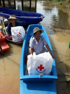 People affected by flooding in Thailand collect provisions from the Thai Red Cross by boat