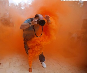 A photo journalist jumps over a smoke canister at a demonstration. REUTERS M. del Pozo courtesy the Thomson Reuters Foundation – Alertnet
